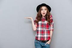 Retrato de una mujer joven chocada sorprendida en camisa de tela escocesa Fotos de archivo