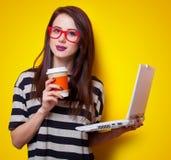 Retrato de una mujer joven con el ordenador portátil y la taza de café Foto de archivo libre de regalías