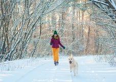 Retrato de una mujer joven con el perro en paseo del invierno foto de archivo