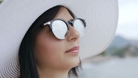 Retrato de una mujer joven con el sombrero y las gafas de sol grandes que goza del sol y del agua Una mujer morena bastante joven almacen de metraje de vídeo
