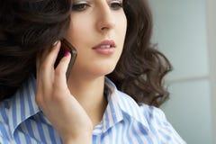 Retrato de una mujer joven con hairdro hermoso que habla en el teléfono móvil foto de archivo libre de regalías