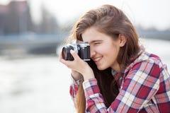 Retrato de una mujer joven con la cámara de la foto Fotos de archivo