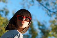 Retrato de una mujer joven con las gafas de sol Foto de archivo