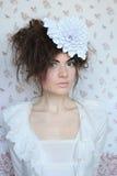 Retrato de una mujer joven con una flor blanca fotos de archivo