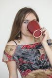 Mujer joven con los ojos verdes hermosos con la taza de café roja Foto de archivo libre de regalías