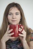 Mujer joven con los ojos verdes hermosos con la taza de café roja Imágenes de archivo libres de regalías