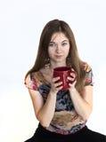 Mujer joven con los ojos verdes hermosos con la taza de café roja Foto de archivo