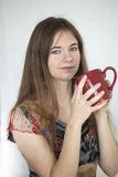 Mujer joven con los ojos verdes hermosos con la taza de café roja Fotografía de archivo libre de regalías