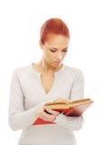 Retrato de una mujer joven del redhead que lee un libro Fotografía de archivo