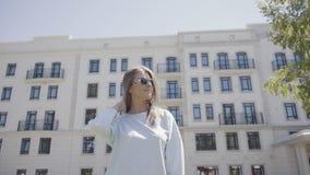 Retrato de una mujer joven elegante y moderna en gafas de sol de la moda almacen de video