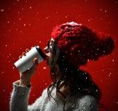 Retrato de una mujer joven en café de consumición del paño del invierno foto de archivo