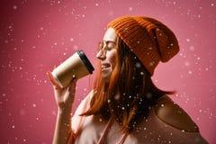 Retrato de una mujer joven en café de consumición del paño del invierno fotografía de archivo libre de regalías