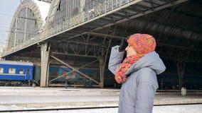 Retrato de una mujer joven en capa azul y sombrero colorido en el ferrocarril durante día de invierno soleado Concepto del viaje metrajes