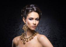 Retrato de una mujer joven en joyas y maquillaje fotos de archivo libres de regalías