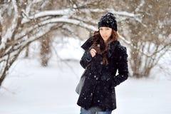 Retrato de una mujer joven en parque del invierno Imágenes de archivo libres de regalías