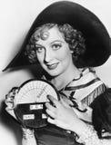 Retrato de una mujer joven en un sombrero que sostiene un velocímetro nuevamente inventado (todas las personas representadas no s Imagen de archivo libre de regalías