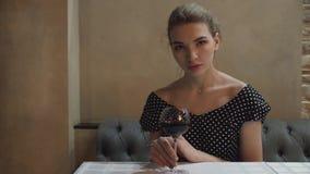 Retrato de una mujer joven en un vestido de noche en un restaurante con gestos atractivos de la copa de vino y miradas blandas almacen de video