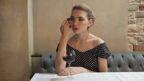 Retrato de una mujer joven en un vestido de noche en un restaurante con gestos atractivos de la copa de vino y miradas blandas almacen de metraje de vídeo