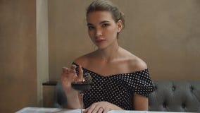 Retrato de una mujer joven en un vestido de noche en un restaurante con la copa de vino metrajes