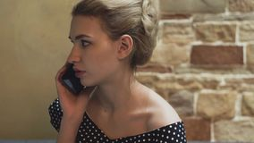 Retrato de una mujer joven en un vestido de noche en un restaurante Ella habla por smartphone metrajes