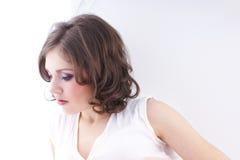 Retrato de una mujer joven en una alineada blanca fotos de archivo