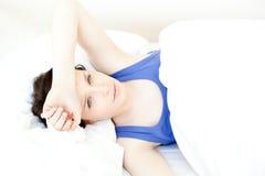 Retrato de una mujer joven enferma que miente en su cama Foto de archivo
