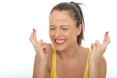 Retrato de una mujer joven feliz con sus fingeres cruzados Imagen de archivo libre de regalías