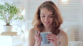 Retrato de una mujer joven feliz, ella bebe el café por la mañana almacen de metraje de vídeo