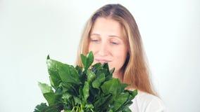 Retrato de una mujer joven feliz hermosa con un ramo de espinaca fresca almacen de video