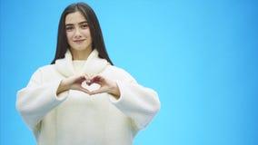 Retrato de una mujer joven feliz que lleva un suéter caliente blanco Durante este tiempo, un gesto de mano del corazón muestra y  almacen de metraje de vídeo