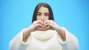 Retrato de una mujer joven feliz que lleva un suéter caliente blanco Durante este tiempo, un gesto de mano del corazón muestra y  metrajes