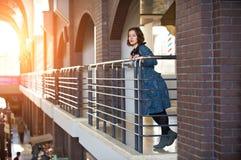 Retrato de una mujer joven feliz que se coloca en el pasillo en la puesta del sol Fotografía de archivo