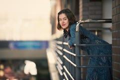Retrato de una mujer joven feliz que se coloca en el pasillo en la puesta del sol Foto de archivo libre de regalías