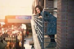 Retrato de una mujer joven feliz que se coloca en el pasillo en la puesta del sol Fotos de archivo