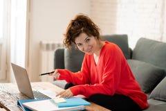 Retrato de una mujer joven feliz que trabaja en el ordenador portátil que se sienta en el sofá En trabajo y concepto del estudio imagen de archivo