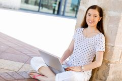 Retrato de una mujer joven feliz que usa el ordenador portátil al aire libre Fotos de archivo libres de regalías