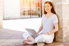 Retrato de una mujer joven feliz que usa el ordenador portátil al aire libre Imagen de archivo