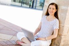 Retrato de una mujer joven feliz que usa el ordenador portátil al aire libre Fotografía de archivo libre de regalías