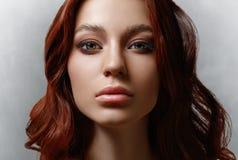 Retrato de una mujer joven hermosa con el pelo del vuelo Muchacha linda que presenta en un fondo gris Ojos hermosos grandes y maq fotos de archivo libres de regalías