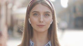 Retrato de una mujer joven hermosa con los auriculares inalámbricos que miran con en la cámara y la situación sonriente en el vie almacen de metraje de vídeo