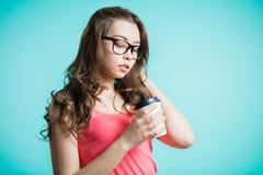 Retrato de una mujer joven hermosa con una taza de café que se coloca en el fondo azul Imagen de archivo libre de regalías
