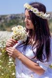 Retrato de una mujer joven hermosa en campo de la manzanilla Muchacha feliz que recoge margaritas Una muchacha que descansa en un foto de archivo