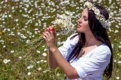 Retrato de una mujer joven hermosa en campo de la manzanilla Muchacha feliz que recoge margaritas Una muchacha que descansa en un fotos de archivo