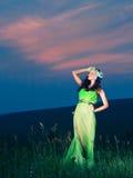 Retrato de una mujer joven hermosa en el fondo de la puesta del sol Foto de archivo