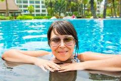 Retrato de una mujer joven hermosa en gafas de sol en la piscina Imagen de archivo
