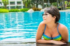 Retrato de una mujer joven hermosa en gafas de sol en la piscina Imagen de archivo libre de regalías