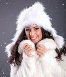 Retrato de una mujer joven hermosa en un abrigo de pieles blanco sobre sno fotografía de archivo