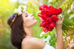 Retrato de una mujer joven hermosa en una guirnalda de la flor de la primavera fotografía de archivo libre de regalías
