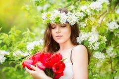 Retrato de una mujer joven hermosa en una guirnalda de la flor de la primavera foto de archivo libre de regalías