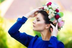 Retrato de una mujer joven hermosa en una guirnalda de rosas, outdoo Fotografía de archivo libre de regalías